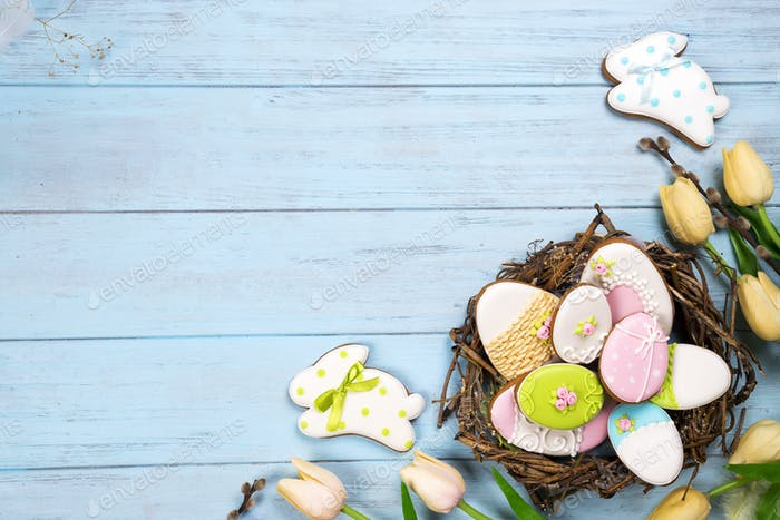Beautiful e tulips with colorful eggs in nest and cookies as bunny on blue wooden background