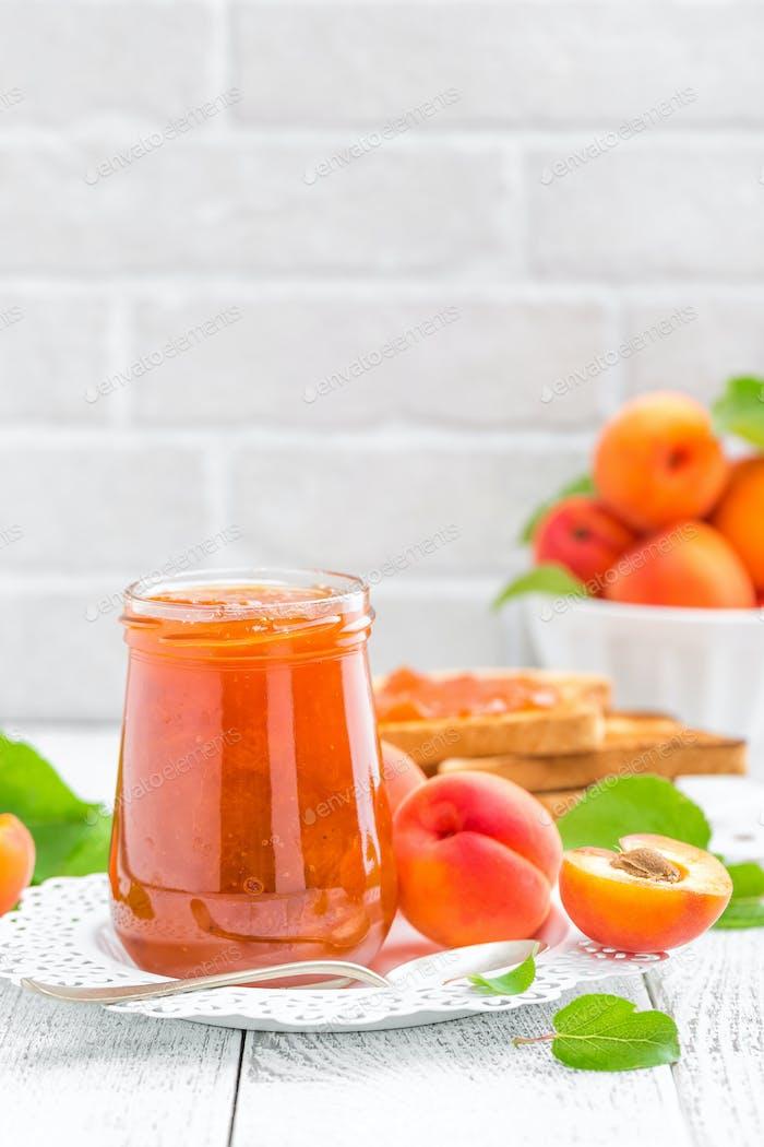 Aprikosenmarmelade in einem Glas und frische Früchte mit Blättern auf weißem Holztisch, Frühstück