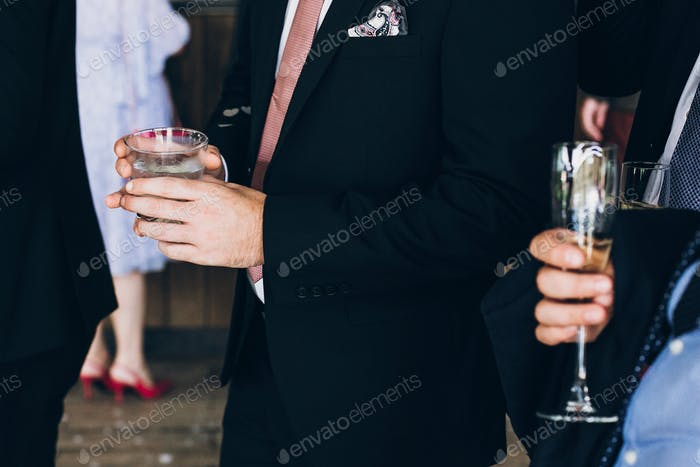 hands of stylish people cheering with glasses of champagne