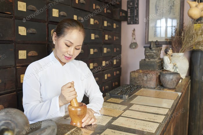 woman grinding up ingredients in mortar