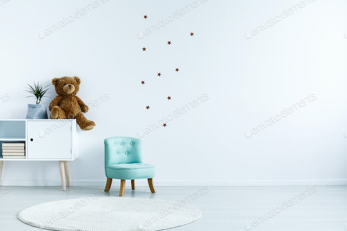 Small light blue armchair for kid standing in white room interio