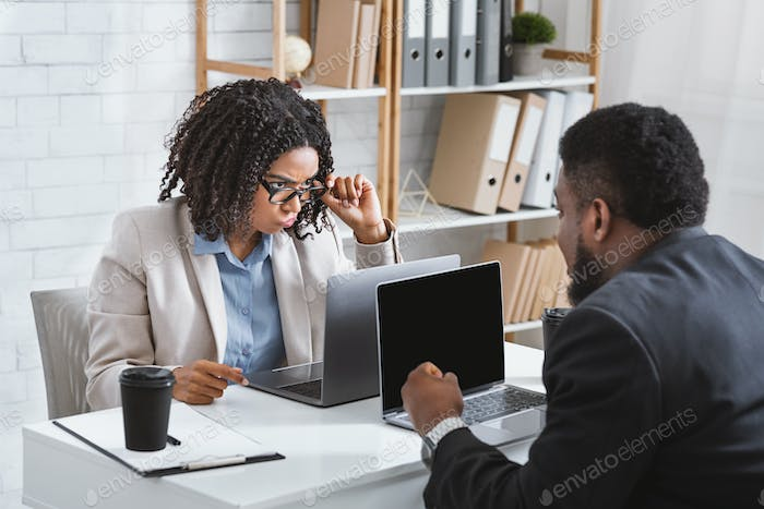 Millennial African American businesswoman having conflict with collague at workplace, empty space