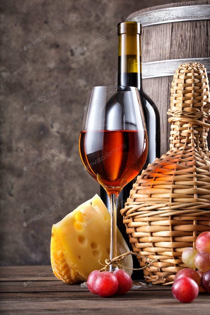 Glas Rotwein mit Flasche und Fass auf dem Tisch