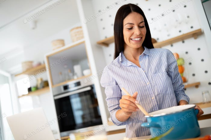Beautiful young woman is preparing food in kitchen at home. Healthy food, diet concept