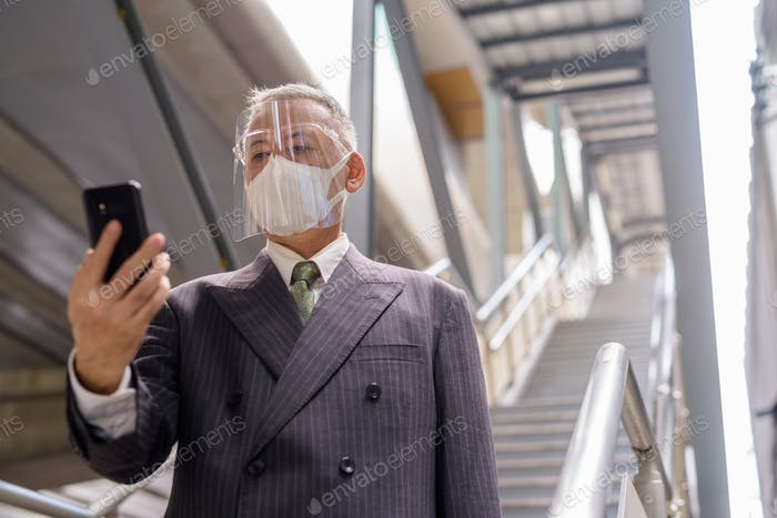 Mature Japanese businessman with mask and face shield using phone while going down the staircase