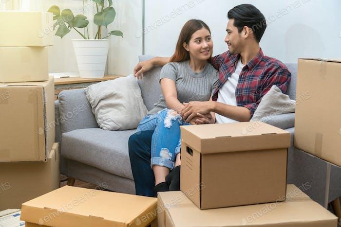 Asiatisches junges Paar, das nach dem Erfolg auf dem Sofa sitzt und große Pappschachtel verpackt