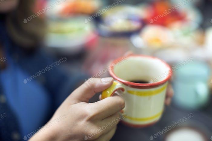 One person at a picnic table outdoors, holding a china mug.