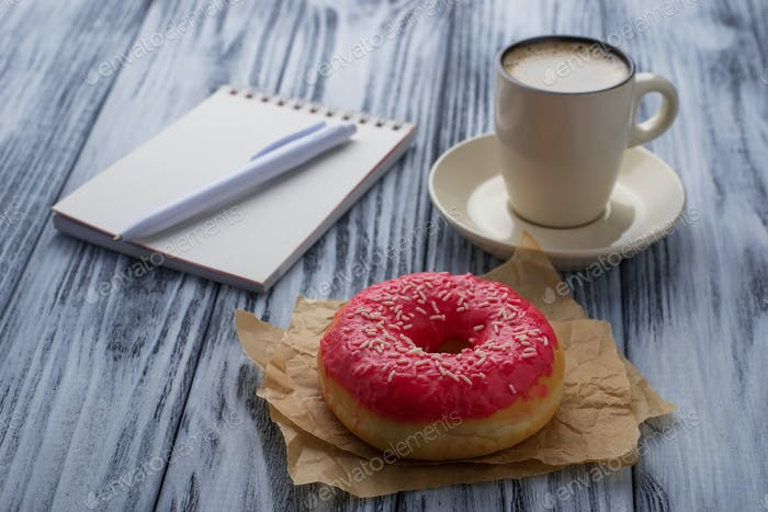 Donut, Tasse Kaffee und Notizbuch