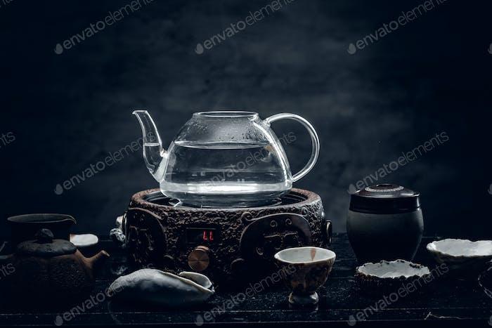 Glass transparent teapot and exotic ceramic mugs.