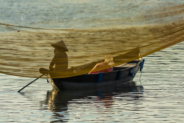 Vietnamese woman in traditional bamboo hat rowing on the Thu Bon River