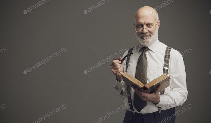 Smiling professor smoking a pipe and reading