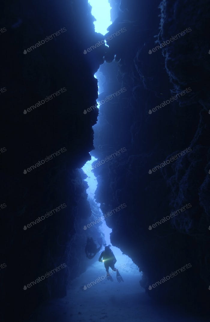 Dramatic silhouette of diver in reef crevice.