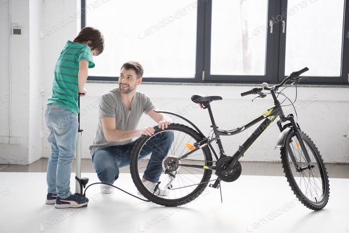 Happy father looking at son inflating bicycle tire with pump indoors