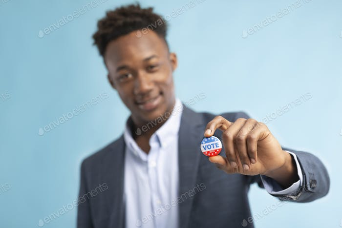 African american man showing vote pin, blurred background