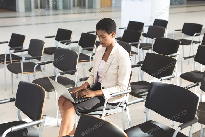 Side view of African American businesswoman sitting on chair and using laptop in lobby at company