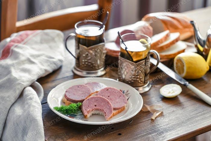 Sandwiches mit geschnittener Wurst auf einem Teller mit Tee