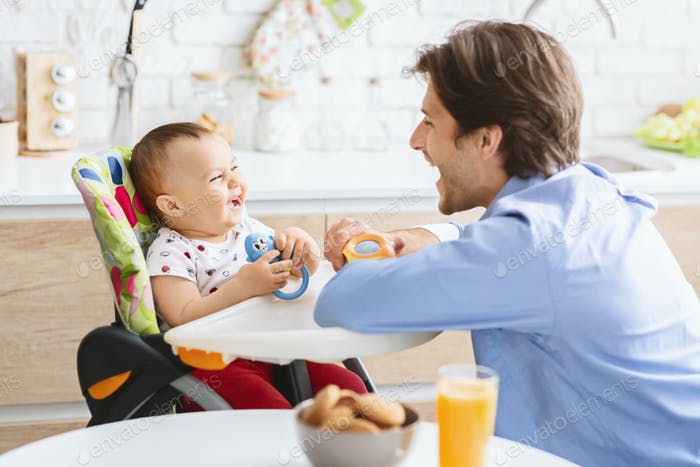 Dad playing with his adorable baby son in kitchen