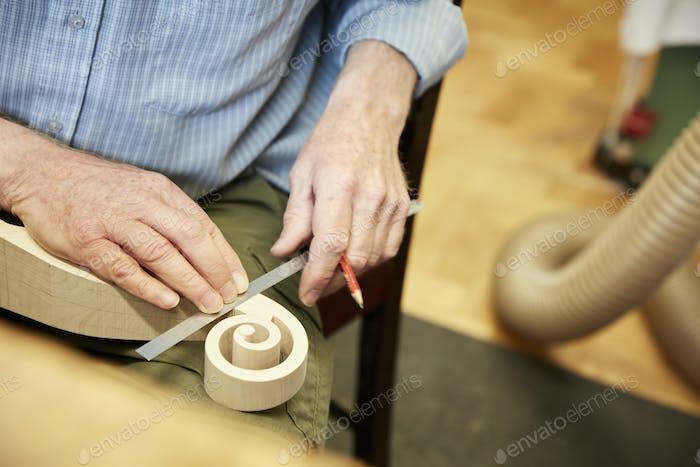 Создатель скрипки, использующий линейку для измерения свернутого свитка скрипки.