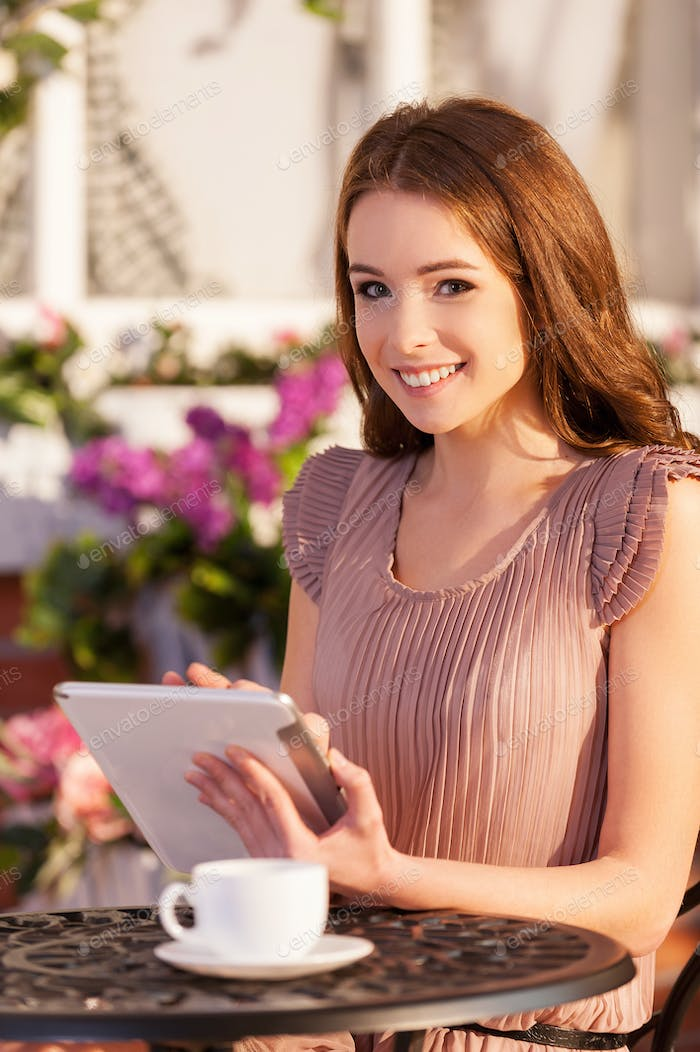 Surfing web in cafe. Cheerful young woman sitting at the outdoor café and using digital tablet
