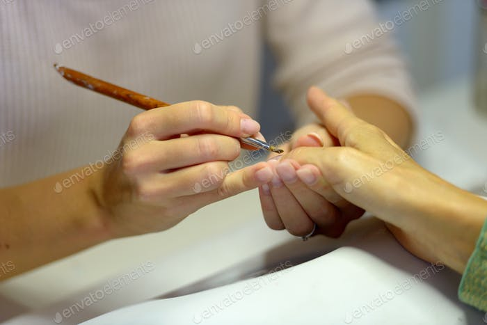 Hands of woman manicurist and customer showing manicure procedure