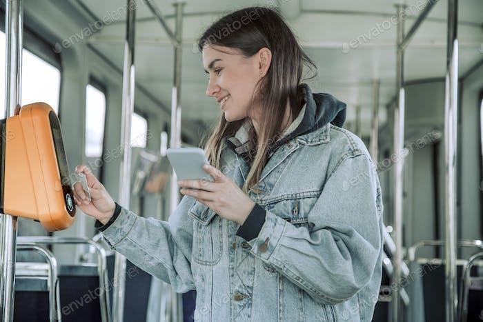 Una joven sin contacto paga el transporte público.