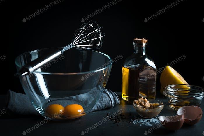 Eigelb in einer Glasschale, Schneebesen zum Schlagen, Olivenöl
