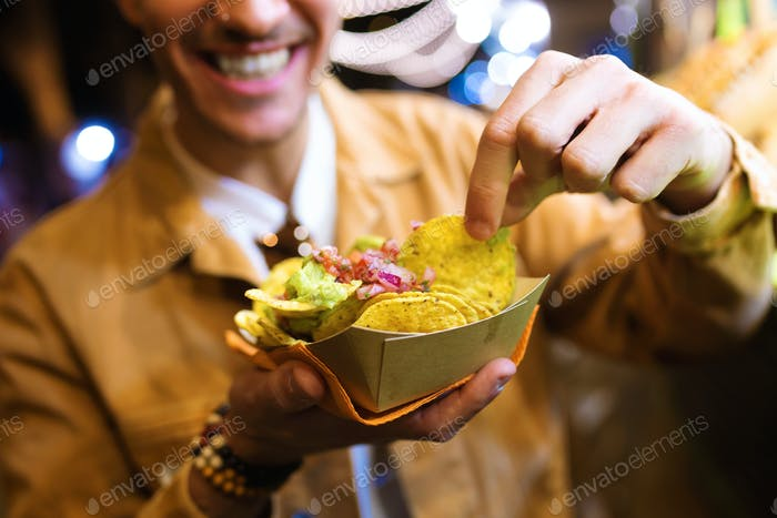 Attractive young man visiting eat market and eating nachos in the street.