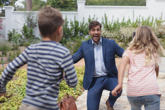Rear view of Caucasian children running towards happy Caucasian father in the garden
