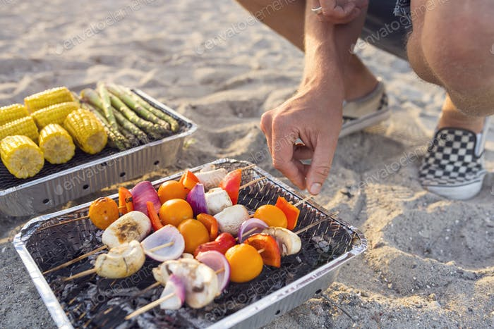 Man (4-5) barbecuing on beach