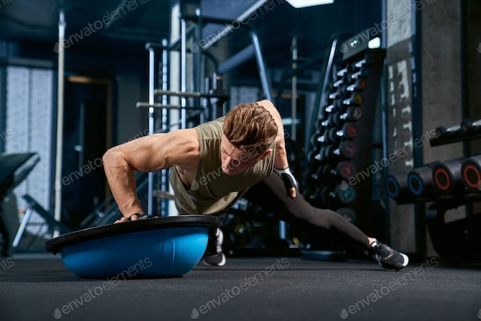 Muscular man doing push ups on one hand
