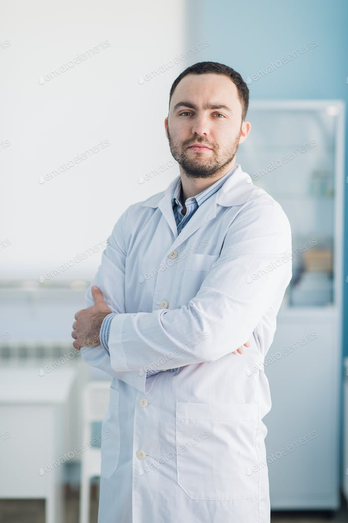 Young handsome doctor indoors at hospital office