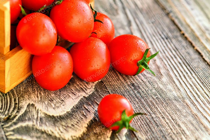 Red ripe tomatoes spill out of box. Rustic view