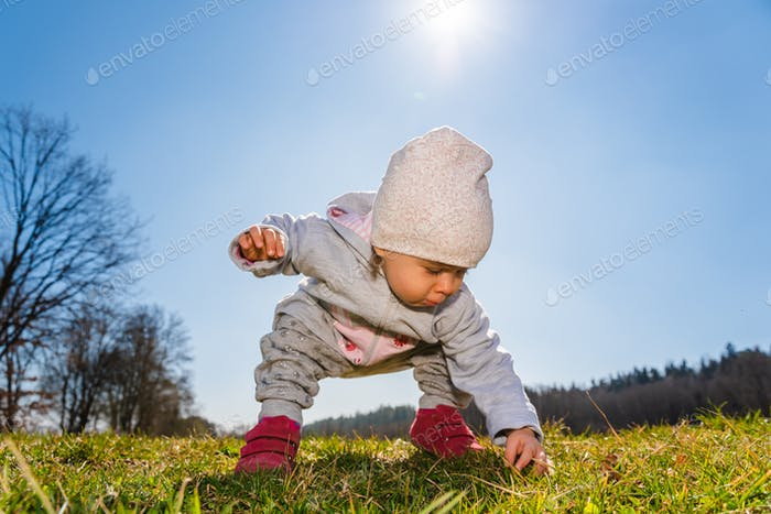 Baby wearing warm beanie hat, sweatshirt and red boots outdoors in rural area discovering nature in