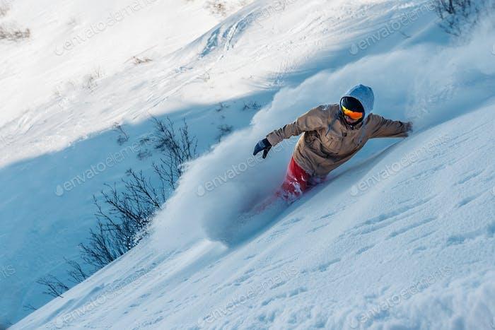 Snowboarder fährt vom Schneehügel