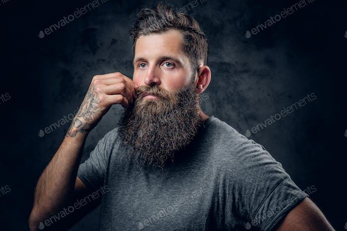Мужчина трогает усы на сером фоне.