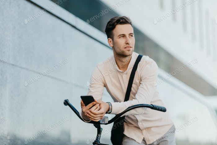 Attractive serious businessman on bicycle with bag, holds smartphone and looks away