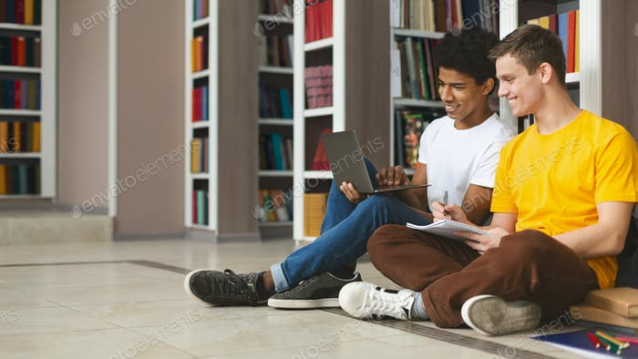 Two young guys studying on floor in library