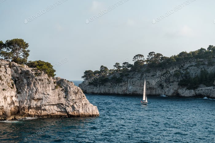 Rock, sea, trees and sailboat of Provence