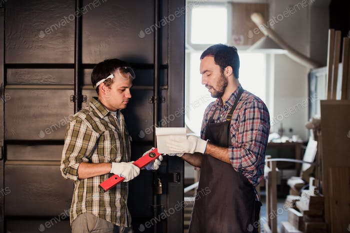 Two carpenters are talking while holding papers and ruler. One of them is wearing safety mask