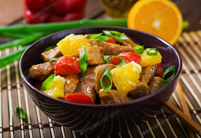 Veal fillet - stir fry with oranges and paprika in sweet and sour sauce on a wooden background.