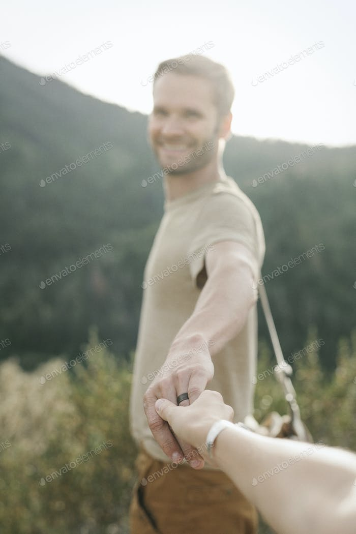 A man holding out his hand to a companion.