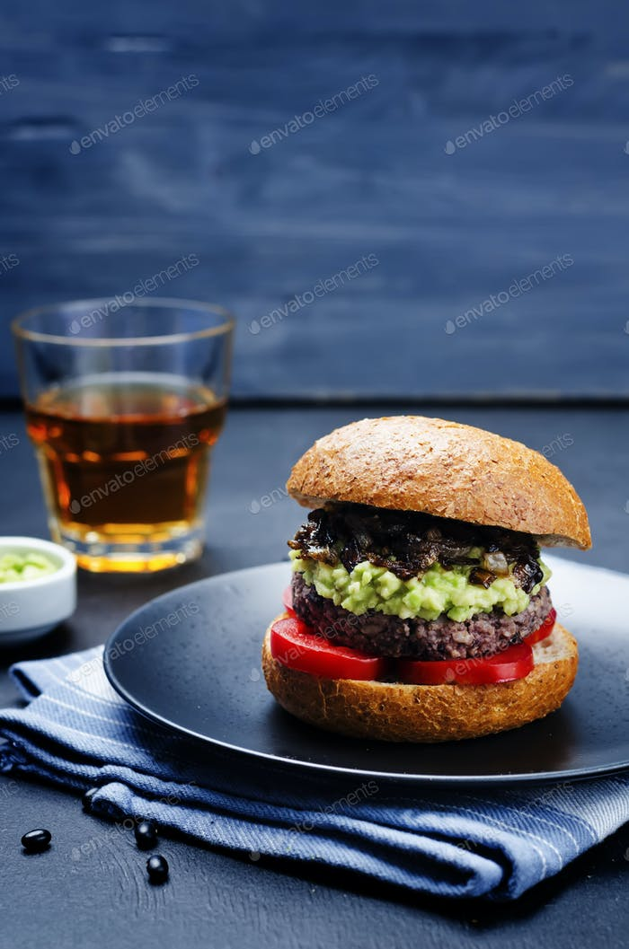 black bean burger with mashed avocado, caramelized onions and to