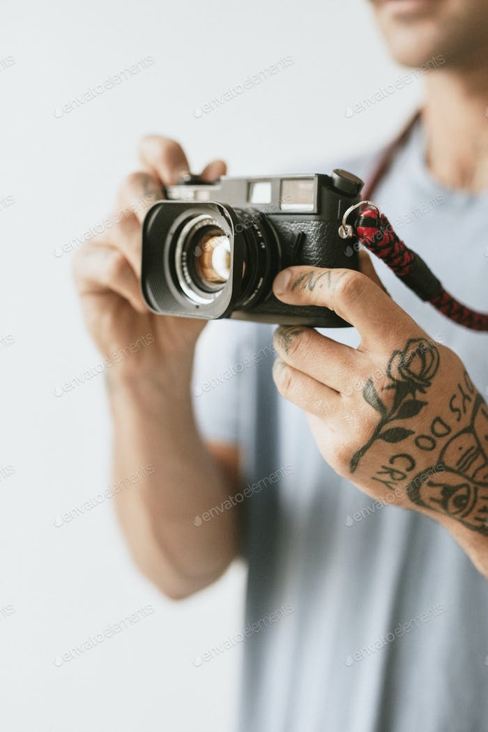 Photographer with tattoos shooting with a film camera