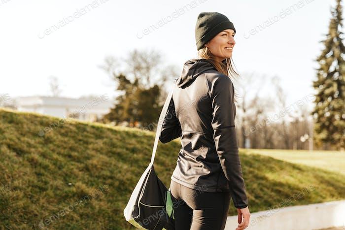 Photo of joyous athletic girl in black sportswear, walking with