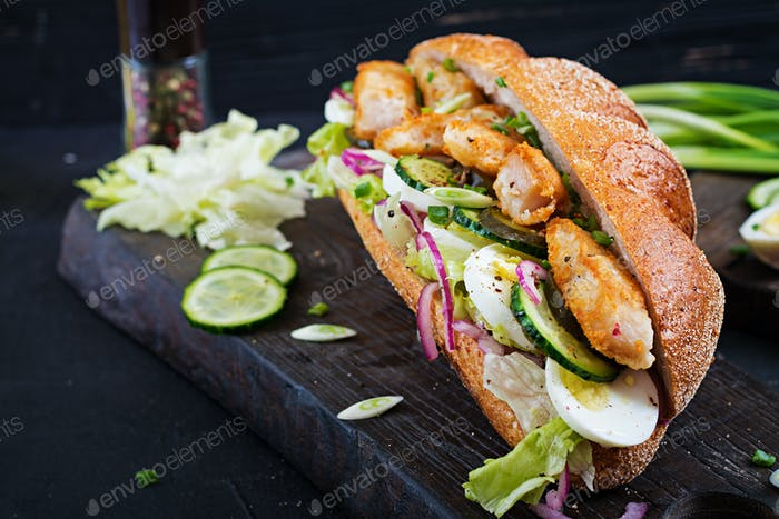 Baguette sandwich with fish, egg, pickled onions and lettuce leaves.