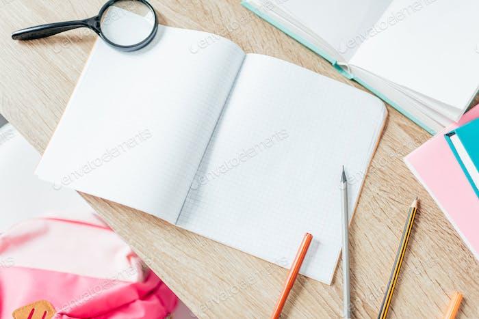 Schreibtisch mit Schulbedarf und offenem Notizbuch darauf gelegt.