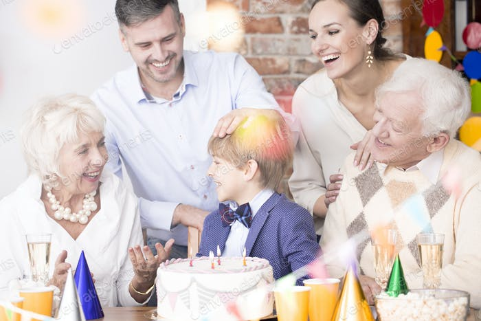 Family sitting beside birthday cake