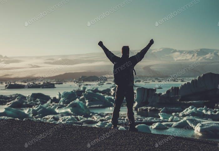 Man explorer lookig at Jokulsarlon lagoon, Iceland.