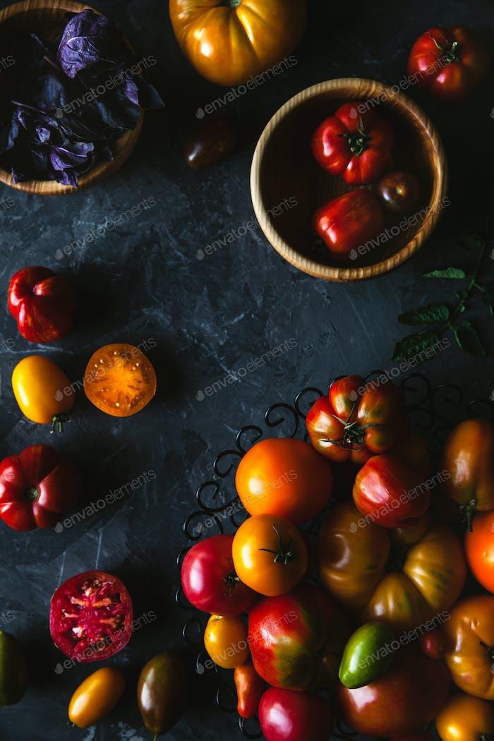 Komposition mit leckeren Tomaten, Holzbrett und Produkten auf grauem Hintergrund, gesundes Essen