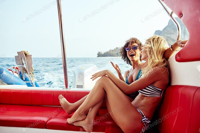 Laughing female friends having fun on a boat during vacation